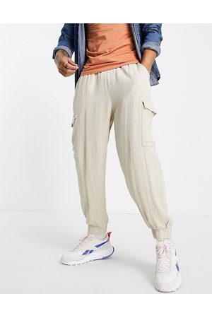 ASOS Teksturerede, oversized, tapered bukser med cargolommer i -Neutral