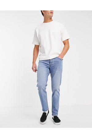 ASOS DESIGN Tapered jeans med stretch i mellemvask-Blå